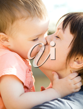 Portrait of a happy mother with her son kissing outdoors