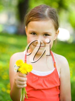 Cute little girl with a bunch of dandelions outdoors