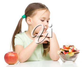 Cute little girl choosing between apples and sweets, isolated over white