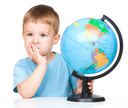 Little boy with a globe, isolated over white