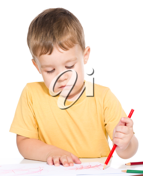 Little boy is drawing using color pencils, isolated over white