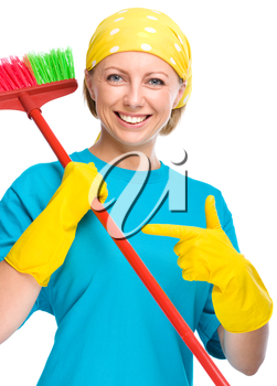 Young woman as a cleaning maid pointing to her broom, isolated over white
