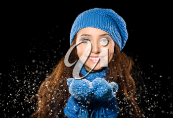Young happy woman under snowfall, isolated over black