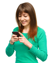 Young cheerful woman is typing sms message on her phone, isolated over white