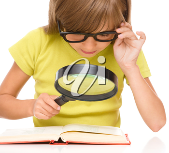 Little girl is reading book using magnifier while sitting at table, isolated over white