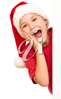 Little girl is holding her face in astonishment standing near blank board, isolated over white