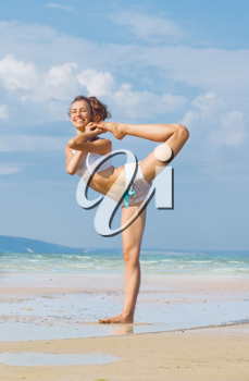 Royalty Free Photo of a Woman Doing Yoga on the Beach