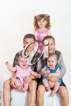 Studio portrait of happy family - brothers and sisters different ages on light background