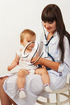 Pediatrician woman doctor with baby girl patient on light background