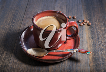 Coffee cup and beans on grunge oak wooden background