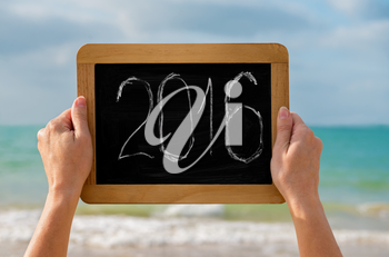 woman's hands with chalkboard and digits 2016 on it against the sea  - concept of new year, vacation and travel