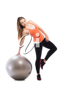 Young sporty woman posing with fit ball. Isolated on white