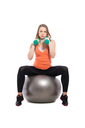 Young beautiful woman sitting on a fit doing exercises with dumbbells. Isolated