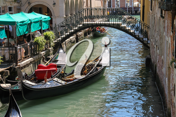 Venice, Italy - August 13, 2016: Empty gondola on canal in city centre