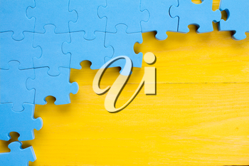 Puzzle on yellow wooden background.Team business concept