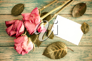 Old roses bouquet and blank greeting card over wooden table. Top view with copy space
