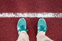 Feet are on the stadium track with a white stripe