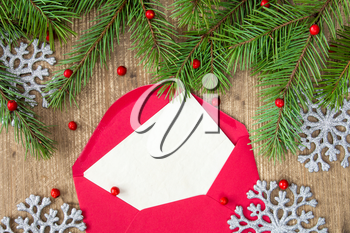 Fir branch,silver shiny snowflakes and red envelope with a blank letter