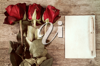 Faded roses and blank paper sheets with pen on wooden background