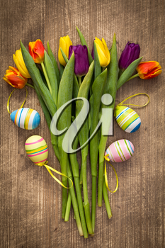 Easter eggs and colorful tulips bouquet on wooden background
