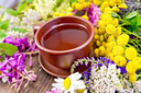 Herbal tea in a clay cup of fresh flowers fireweed, tansy, chamomile, clover, yarrow, meadowsweet, mint leaves on a wooden boards background