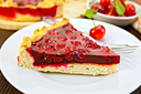 Piece of sweet pie with cherries and jelly in a white plate with a fork on the background of wooden boards