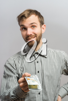 Portrait of smiling young man holding fanned US paper currency