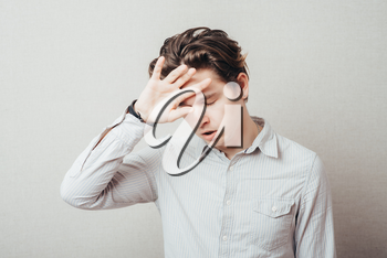 Handsome man with headache and the hand on forehead isolated on a white background