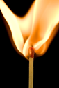 Macro of an ignited matchstick flame in the dark