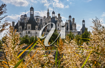Chateau de Chambord backlighted from grass, the largest royal Renaissance french castle in Loire Valley, France