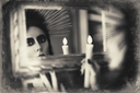 Beautiful goth girl holding candle in hand and looking into the mirror. Grunge texture effect