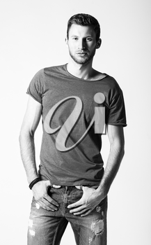 Studio fashion shot: portrait of a handsome young man wearing jeans and shirt. Black and white