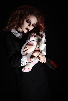 Horror shot: a sad gothic girl with rabbit toy and bloody knife in hands