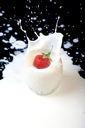 Royalty Free Photo of a Strawberry in Splashed Milk