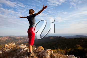 Royalty Free Photo of a Woman Standing on Top of a Mountain