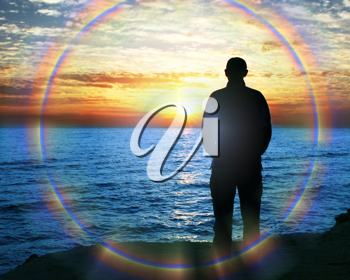 Royalty Free Photo of a Silhouette of a Man Standing Beside the Sea at Sunset