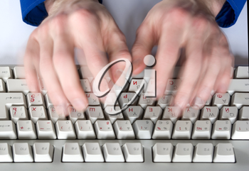 Fingers type a text on the computer keyboard