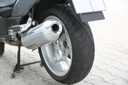 Black wheel of a motorcycle with the chromeplated muffler the rear view