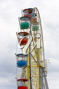 Brightly colored Ferris wheel against a background of clouds