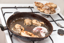 fish is fried in a pan in butter