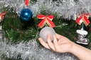 toy on the Christmas tree in a child's hand for the New Year