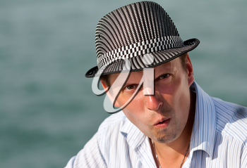 portrait of a man in a hat amazed at the background of the azure sea