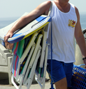 Royalty Free Photo of a Man Carrying Beach Chairs