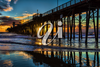 Royalty Free Photo of an Oceanside Pier at Sunset