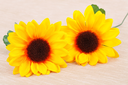 Yellow fabric daisies on beige cloth background.