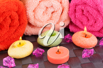 Spa set with towels, candles and stones on bamboo background.
