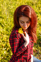 Young pretty woman with yellow daisy flowers in field.