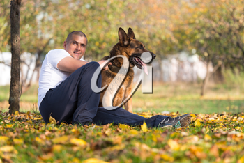 Adult Man Sitting Outdoors With His German Shepherd