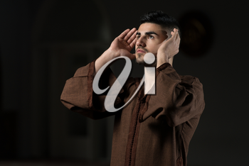 Young Muslim Man Making Traditional Prayer To God While Wearing A Traditional Cap Djellaba