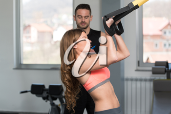 Personal Trainer Showing Young Woman How To Train With Trx Fitness Straps In A Gym